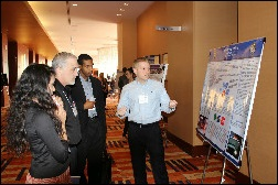 Joe Kropff presents his poster to Dominic Walker and other sociologists at the Eastern Sociologcal Society meetings.