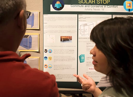 A student talks with a man in the foreground, while a poster for SolarStop can be seen in the background