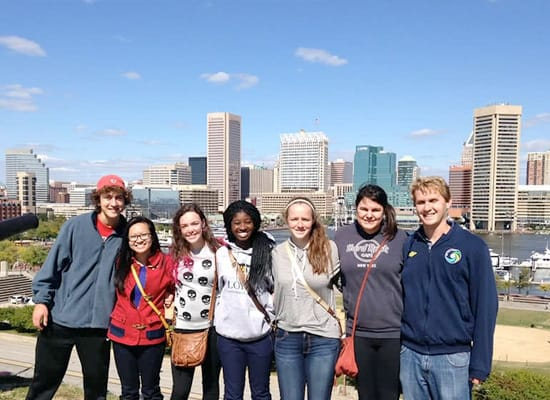 A group of students posing for a photo, with the harbor and Baltimore skyline in the background
