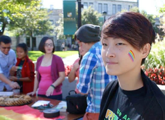 A student with a rainbow painted on her cheek with other students blurred in the background