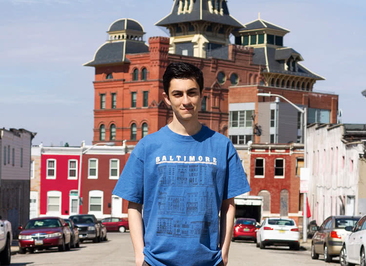 Andrew standing in front of brick buildings in Baltimore