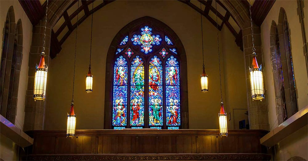 Stained glass and hanging lanterns light up the interior of the Alumni Memorial Chapel