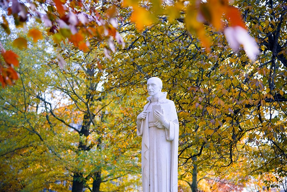 The St. Ignatius statue on the quad framed by fall foliage