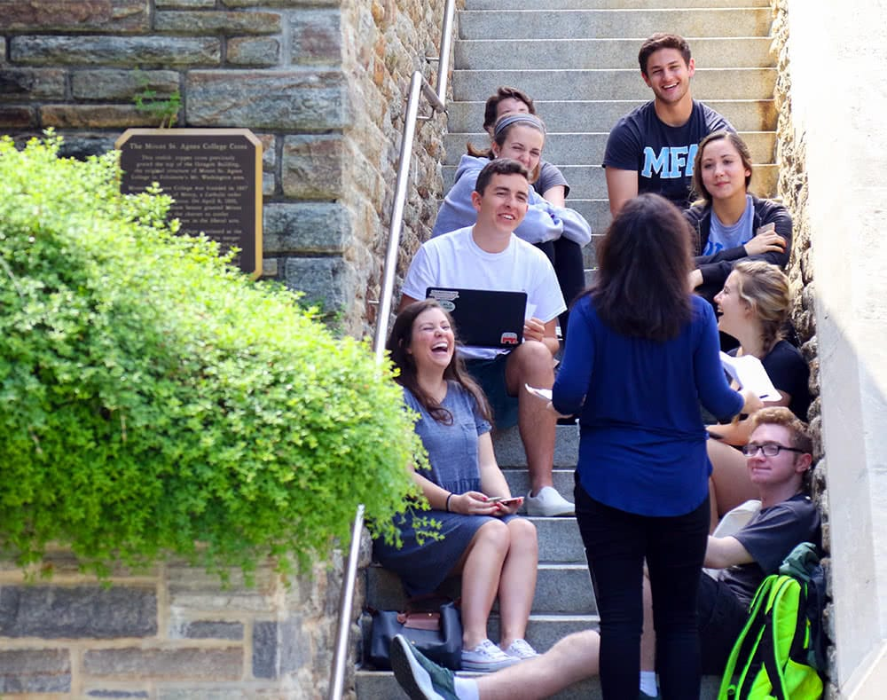 A professor teaches a small class outdoors, with the students sitting on concrete stairs in front of her