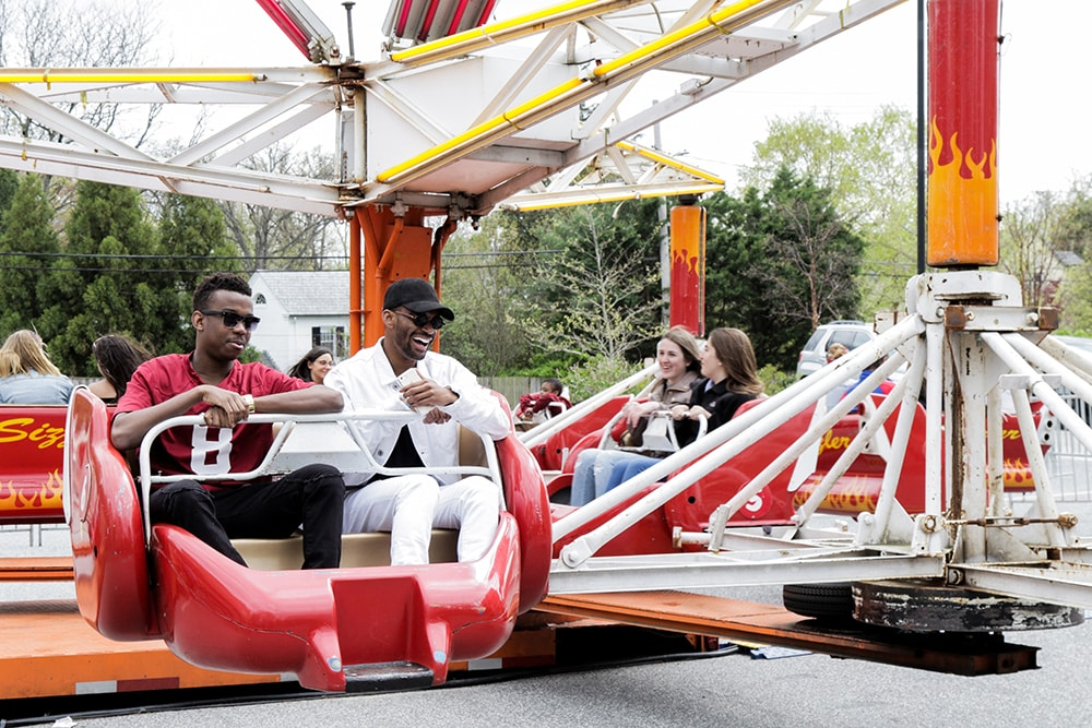 Students laughing and riding on an amusement ride at Loyolapalooza