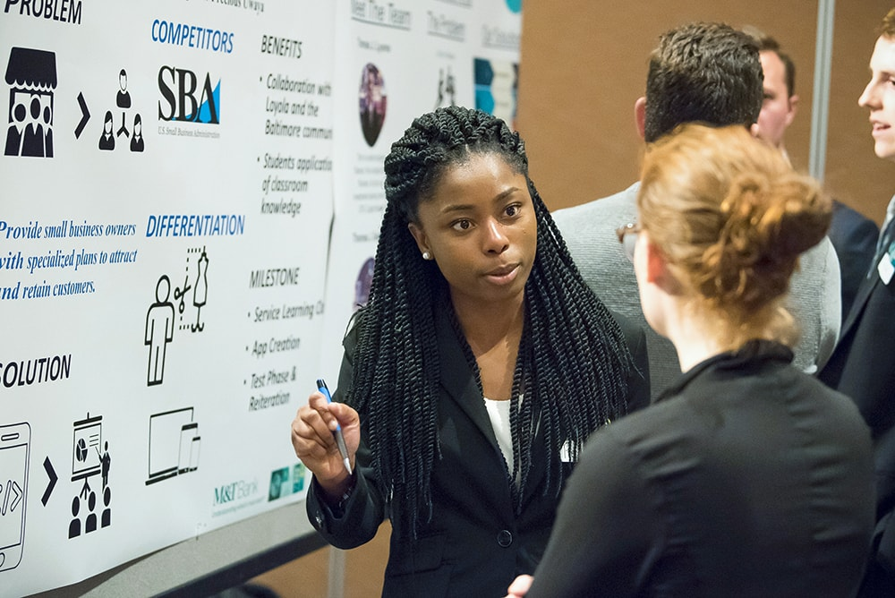 A student standing in front of a presentation board speaking to visitors at a Pitch Competition