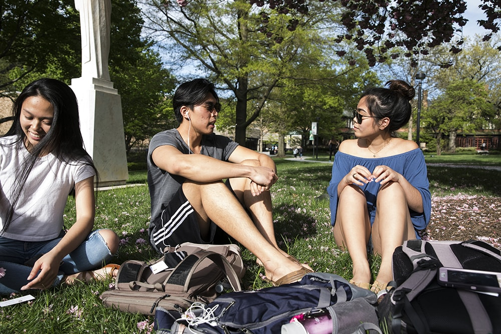 Students sitting on the grass conversing during a sunny day on the quad