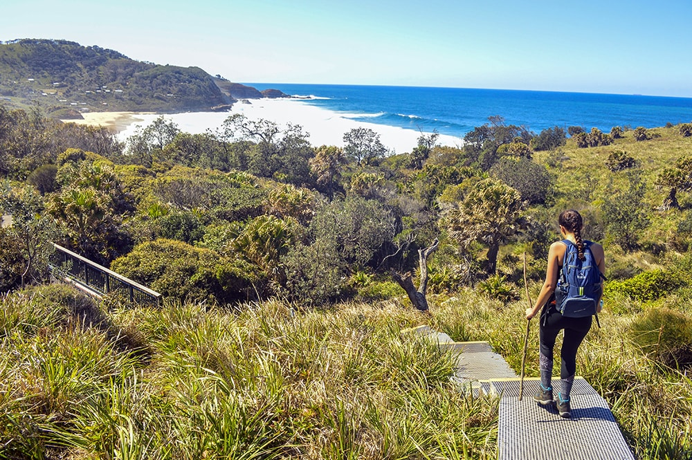 Study abroad student hiking towards a scenic beach in Sydney, Australia