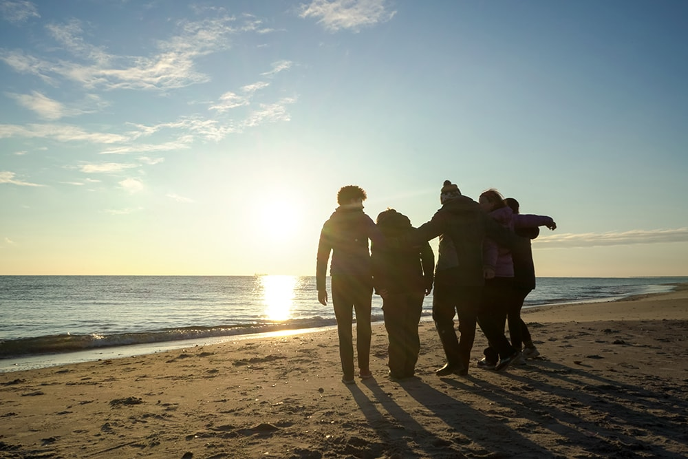 A silhouetted group of students with their arms around each other near the waterline on a beach