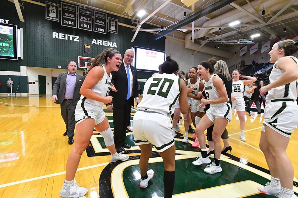 Members of Loyola's women's basketball team in a group celebration on the court of Reitz Arena