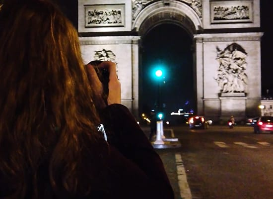 Student testing out lighting techniques while taking a photo of the Arc de Triomphe in Paris at night
