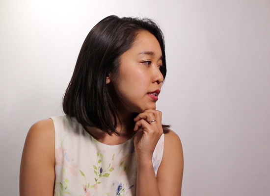 A female professor looks to the side in front of a white backdrop