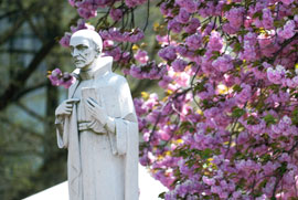 Statue of Ignatius next to spring flowers
