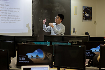 A professor teaching in front of a blackboard and projection screen