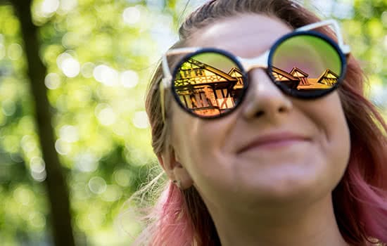 A smiling student, with the reflection of the Humanities Building in her sunglasses