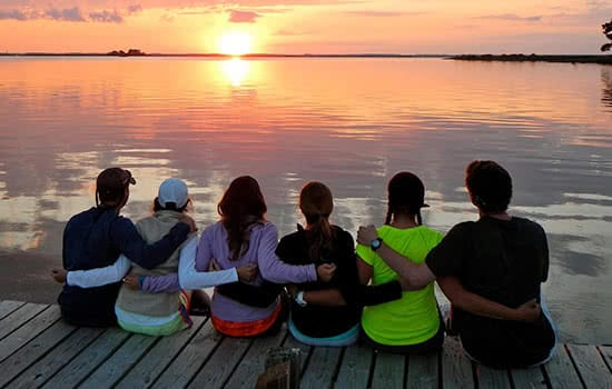 Students sitting on a dock looking at the sunset