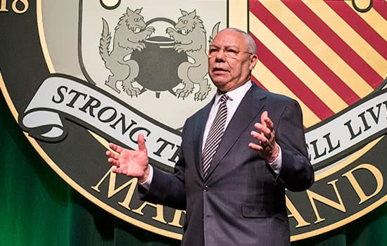 Colin Powell speaking on stage at Loyola